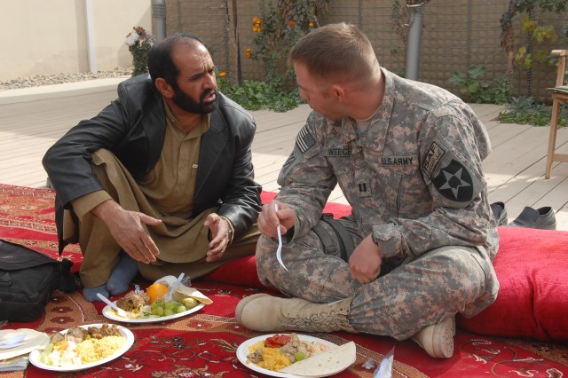 Capt. Adam Weece (right), public affairs officer for the 5th Stryker Brigade Combat Team, talks with Abdul Tawab Quraishy, representative for FM 88.5 in Lashkar Gah, about future embed possibilities with Stryker Soldiers in the area.