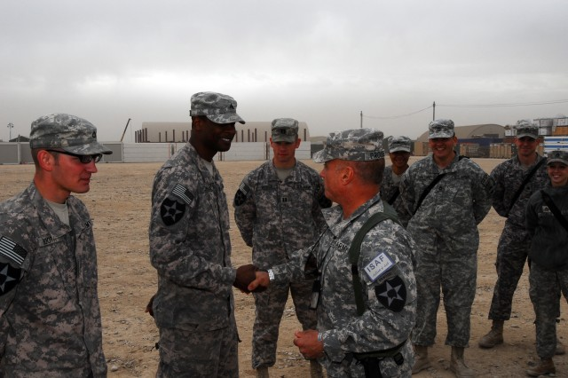 Command Sgt. Maj. Robert Prosser (right front), the senior enlisted Soldier in the 5th Stryker Brigade Combat Team, Afghanistan, presents a brigade coin to Sgt. Chris Florence, following a patch ceremony for members of the brigade's public affairs section.