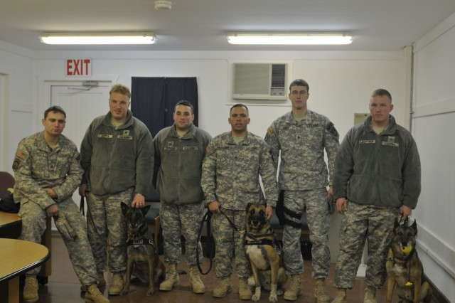 """CAMP BONDSTEEL, Kosovo - Members of Camp Bondsteel's military police K9 team are ready to return home after spending a year here, providing force protection on and off base. Staff Sgt. Carlos Paniagua, Sgt. Tyler Leopold and Spc. Bryan Skipper are all active duty U.S. Army military working dog handlers, who deployed to Kosovo to serve on a NATO peace-support mission working for KFOR 12 Multi-National Task Force-East. Paniagua, 615th Military Police Co., Grafewoehr, Germany, has been the kennel non-commissioned officer in charge (NCOIC) for their team. The three outgoing K9 handlers received Army Achievement Medals from Col. Bob Fode, deputy commander for Multi-National Task Force-East, and Command Sgt. Major Jack Cripe Jr., command sergeant major for Multi-National Task Force-East, for their deployment and exceptional work supporting Camp Bondsteel, Kosovo, during a final farewell, going-away ceremony Jan. 21, the night before they flew back to Germany. """"The service that these Soldiers and their faithful companions have put forth over the past year has been invaluable,"""" Fode said. """"The K9 team worked seamlessly alongside MNTF-E Soldiers and the civilian force protection on Camp Bondsteel to provide a blanket of safety and security that we should never take for granted. Their work both on and off base only added to the efforts that we are all making here to provide a safety and security for all people in Kosovo."""" Before their departure, these handlers and their canine partners showed their replacements the ropes. A member of the 230th Military Police Co.,Kaiserslautern, Germany, Skipper stated that there really isn't a training process to go through. """"We do the same thing here that we do back at our home stations,"""" Skipper said. """"We have to train our dogs daily and meet certain training requirements weekly and monthly."""" """"Training here is the same as anywhere else for dog handlers,"""" Leopold added. """"I'm sure the next guys will be able to pick up right where they left o"""