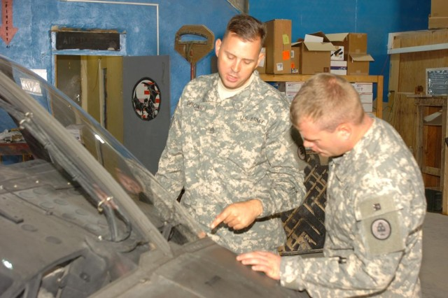 Staff Sgt. Michael Brown (left), maintenance squad leader and OH-58D Kiowa Warrior helicopter maintenance supervisor, Troop F, 1st Squadron, 230th Air Cavalry Squadron, from Maryville, Tenn., and part of the Tennessee Army National Guard, discusses a sheet metal repair on an OH-58D with his Soldier at Forward Operating Base Sykes, Tall Afar, Iraq, Nov. 8. (Photo by: Staff Sgt. Mike Alberts, 25th Combat Aviation Brigade Public Affairs)
