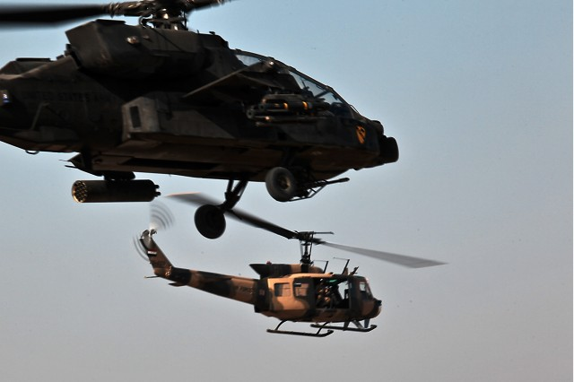 CAMP TAJI, Iraq - An AH-64D Apache attack helicopter (foreground) flies alongside an Iraqi UH-1 Huey (background) during a joint mission between 1st Battalion, 227th Aviation Regiment, 1st Air Cavalry Brigade, 1st Cavalry Division, U.S. Division - Center, and 2nd Squadron of the Iraqi Air Force Jan. 20. (U.S. Army photo by Sgt. Travis Zielinski, 1st ACB, 1st Cav. Div., USD-C)