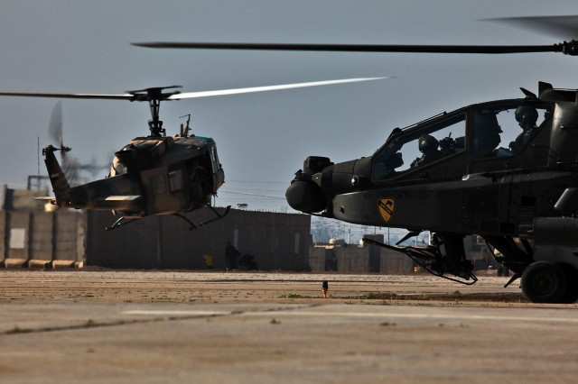 CAMP TAJI, Iraq - Aviators in 1st Battalion, 227th Aviation Regiment, 1st Air Cavalry Brigade, 1st Cavalry Division, U.S. Division - Center, move an AH-64D Apache attack helicopter behind a UH-1 Iroquois helicopter from 2nd Squadron, Iraqi Air Force, before taking off for a joint mission in and around the Baghdad area Jan. 20. (U.S. Army photo by Sgt. Travis Zielinski, 1st ACB, 1st Cav. Div., USD-C)