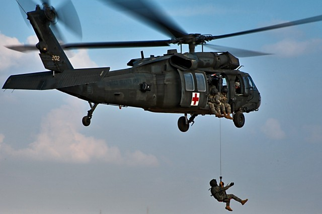 A Soldier dangles from a UH-60 Black Hawk helicopter as he is lowered to the ground during a training exercise conducted by Company C, 2nd Battalion, 227th Aviation Regiment, 1st Air Cavalry Brigade, 1st Cavalry Division, Jan. 21. The training was conducted from several different altitudes so the helicopter crews could familiarize themselves on hoist operations.