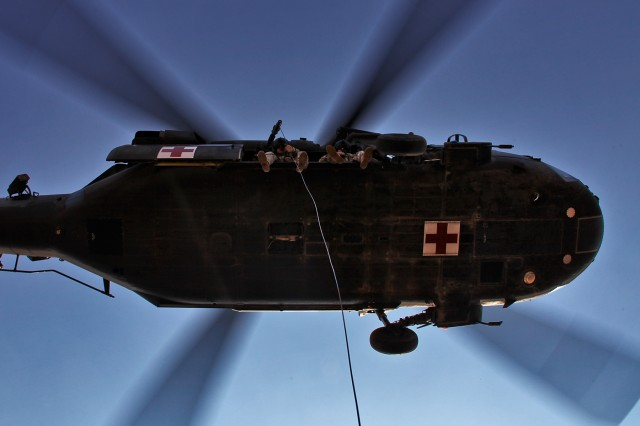 During a hoist training exercise, Staff Sgt. John Presas (left), from San Antonio, Texas, a flight medic, and Staff Sgt. Luis Torres (right), from Las Cruces, N.M., a Black Hawk crew chief, both of whom are in Company C, 2nd Battalion, 227th Aviation Regiment, 1st Air Cavalry Brigade, 1st Cavalry Division, lower a Soldier to the ground from a UH-60 Black Hawk helicopter Jan. 21. The training was done to familiarize the crew with hoist operations.