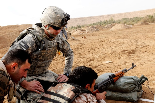 Staff Sgt. Jeffrey Grant, a section sergeant assigned to Troop C, 1st Squadron, 89th Cavalry Regiment, 2nd Brigade Combat Team, 10th Mountain Division, observes the breathing techniques of an Iraqi Army soldier as he zeroes a rifle during advanced marksmanship training at Contingency Operating Station Cashe South, Jan. 11. The training is designed to enhance the firing capabilities of Iraqi forces who have had limited training opportunities.