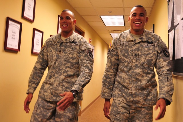 Staff Sgt. Baron Fulp walks with his twin brother Staff Sgt. Braulio Fulp down a hallway in the headquarters offices of the 289th MP Company at Fort Myer. The twins, serving together over most of their careers, reenlisted last month to continue careers that have matched their early dreams.