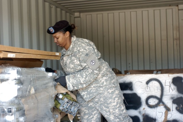 Sgt. Anesa Martin, Third Army G-5 Knowledge Management noncommissioned officer, unloads cots from a connex at Fort Gillem, Ga., Jan. 25. In keeping with its mission to provide humanitarian assistance, Third Army is sending the cots to Haiti to aid relief efforts.