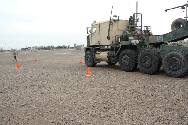 A Soldier from the 1483rd Transportation Company, 541st Combat Sustainment Support Battalion, 15th Sustainment Brigade, 13th Sustainment Command (Expeditionary), knocks over cones while attempting to do straight-line backing with a heavy equipment transporter Dec. 29 on Camp Taji, Iraq, as Sgt. Josephine Beal, an operator with the 1483rd Trans. Co. and Ohio native, sets the cones back up and grades the driver. (Courtesy photo)