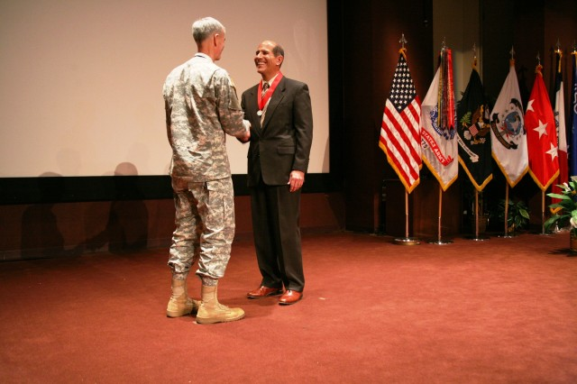 Lt. Gen. Kevin T. Campbell, U.S. Army Space and Missile Defense Command/Army Forces Strategic Command commanding general, shakes hands with Ivan Romero, deputy director, Test and Warfighter Solutions Center, after awarding him the Honorable Order of Saint Barbara during the Town Hall on Jan. 21 at the Bob Jones auditorium.
