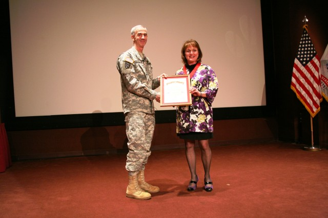 Lt. Gen. Kevin T. Campbell, U.S. Army Space and Missile Defense Command/Army Forces Strategic Command commanding general, presents Pam Mitchell, chief of protocol, with the Honorable Order of Saint Barbara award during the Town Hall on Jan. 21 at the Bob Jones auditorium.