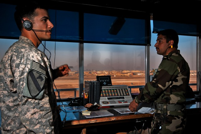 An air traffic controller from 2nd Battalion, 227th Aviation Regiment, 1st Air Cavalry Brigade, receives details of an incoming flight as Iraqi Air Force 2nd Lt. Taha Khaleel, an air traffic controller, watches the flightline for signs of activity in the air traffic control tower.