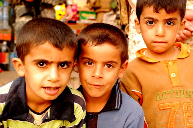 Local children greet soldiers on a joint patrol between the 52nd Iraqi Army Brigade and Military Transition Team 5214 (Bandits) in the Basra Province, Iraq.