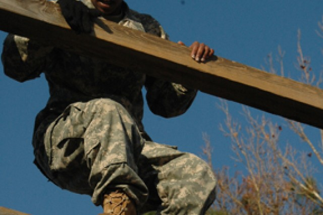 """Spc. Amanda Davis, food service specialist, Troop D, 3rd Squadron, 89th Cavalry Regiment, 4th Brigade Combat Team, 10th Mountain Division, climbs down the """"stairway to heaven"""" at the obstacle course Jan. 7."""