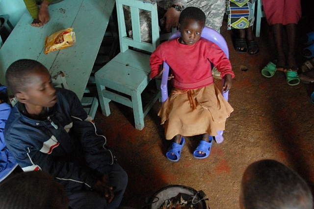 Maj. Mike Walter, USAMRU-K's chief of staff, listens as children at the Agape Children's Home sing. The children, all orphans, live with HIV.