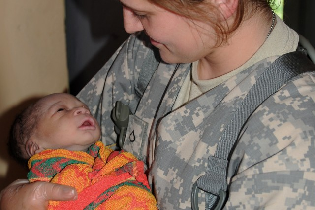 """Pfc. Kendra Hinds, a Reserve medic from Lubbock, Texas, augmenting the 7225th Medical Support Unit, holds 5.5-pound, 15-minute-old """"Cage,"""" a Ugandan infant she helped deliver at the Pajimo Clinic in Kitgum, a rural area in the north. The 19-year-old mother walked to the clinic and delivered him two hours later."""