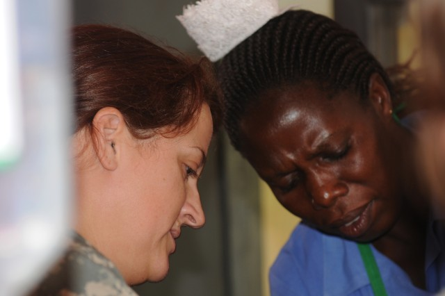 """1st. Lt. Victoria Lynn Watson (left) and Stella Betty Lamono, the midwife at the Pajimo Clinic in rural Kitgum, Uganda, work together to deliver a newborn. The 19-year-old mother arrived at the clinic, run by U.S. and East African medical personnel, and gave birth about two hours later. Watson, a Reserve Soldier with the 7225th Medical Support Unit, is a labor and delivery nurse in her civilian occupation, and was called upon to assist in the delivery. The mother asked Watson to name her son, and Watson chose the name """"Cage."""""""