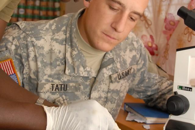 Pvt. Umaru Konneh shows a typhoid tainted blood sample to Staff Sgt. Mike Tatu at Edward Binyah Kesselly Military Barracks, Liberia.