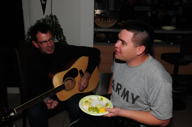 "Sgt. Florentino Valdez, a wounded warrior, talks with Doug Pierce, a member of the Christian band ""Pierce."" The group stopped by the United Service Organizations Warrior Center in Landstuhl  to entertain service members during a special visit where members of the Heidelberg  sports and fitness office cooked dinner for about 80 wounded warriors."