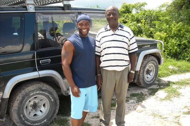 Staff Sgt. Johny Eliscar, left, greets his godfather, Tolem Myrtil, during his most recent visit to Haiti in August. Eliscar's family home, located on the outskirts of Petionville, was spared from the devastation of recent earthquakes in the area.