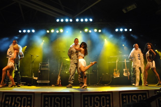 The Dallas Cowboys Cheerleaders bring three airmen on stage for a special dance routine during the USO tour at Chièvres Air Base. The Dallas Cowboys Cheerleaders have been supporting the USO since 1979. Paired left to right: Sarah Gourley and Tech Sgt. Phil Erven, SHAPE Command Group Deputy Chief of Staff Operations; Trisha Trevino and Senior Airman Matthew Heckmann, 309th Airlift Squadron Fire Department; and Nichole Hamilton and Master Sgt. Rick Burgess, NATO Communication and Information Systems Services Agency.