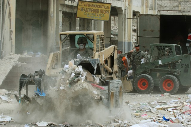 A Paratrooper assigned to A Co., 2nd Brigade Special Troops Battalion, 2nd Brigade Combat Team, removes rubble from the streets of Port-au-Prince, Haiti, Jan 26. The 2BSTB worked with soldiers from 2nd Battalion, 325th Airborne Infantry Regiment, 2BCT and the Center for National Equipment to clear the streets, making it easier to distribute aid to the Haitian people. (U.S. Army photo by Pfc. Kissta M. Feldner, 2BCT PAO)