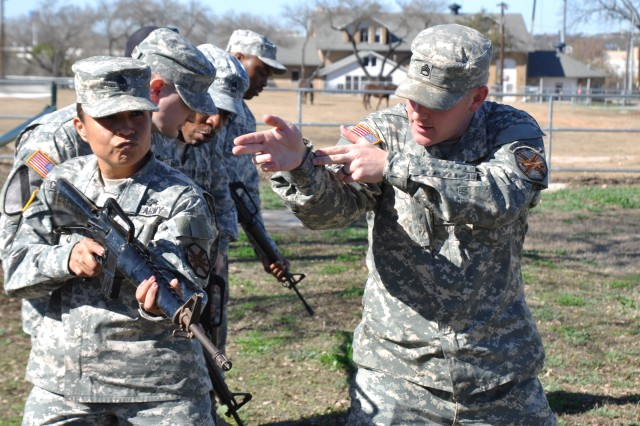 First Sgt. Rosalba Chambers (left) receives room-clearing instructions from Sgt. Ian Comgs during a weekly training with Headquarters and Headquarters Company .
