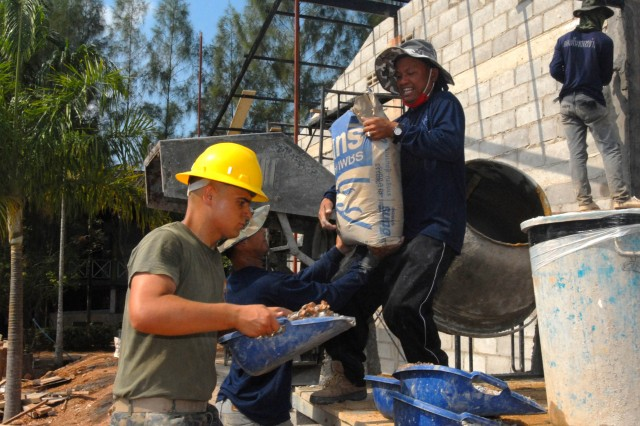 A combat engineer from the 172nd Marine Wing Support Squadron works with Thai combat engineers to construct a building for the Nan Jek Sroi School in Chantaburi province.