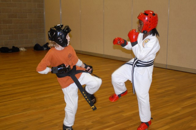 Abigail Agin, 9, left and Briana Grant, 9  Students wear safety equipment to guard against injuries.  Head, hand and foot pads provide a layer of protection during sparring. There are seven belt colors, including white, yellow, green, blue, brown, red and black, that symbolize elements of nature.  Each has multiple levels of proficiency. Stripes are an indication of preparedness to participate in tests to move to the next level.