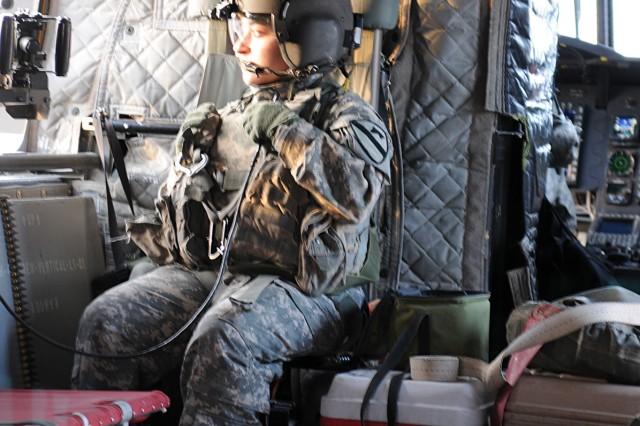 BAGHDAD - Spc. Bernice Garcia, a Houston native and Chinook door-gunner with Company B, 3rd Battalion, 227th Aviation Regiment, 1st Aviation Cavalry Brigade, 1st Cavalry Division, tests her radio Jan. 21, before taking her position in the window to scan her sector.