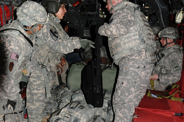 BAGHDAD - Spc. Bernice Garcia, a Houston native and Chinook door-gunner with Company B, 3rd Battalion, 227th Aviation Regiment, 1st Aviation Cavalry Brigade, 1st Cavalry Division, takes control in the Chinook to ensure that all baggage is secured before takeoff Jan. 21.
