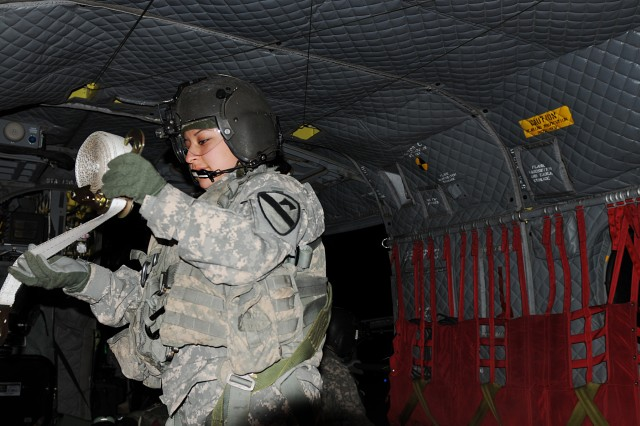 BAGHDAD - Spc. Bernice Garcia, a Houston native and Chinook door-gunner with Company B, 3rd Battalion, 227th Aviation Regiment, 1st Aviation Cavalry Brigade, 1st Cavalry Division, winds a strap back up as part of her cleanup duty as her flight comes to an end Jan. 21 at Camp Taji, Iraq.