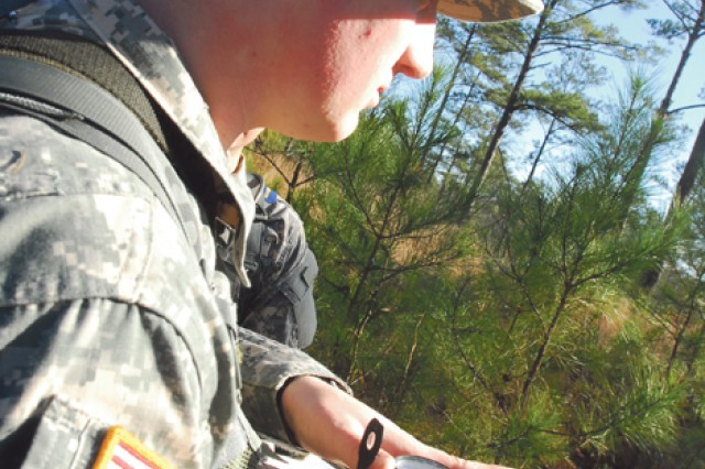 """PFC James Henry uses a lensatic compass to get his bearings Tuesday at Uniform 1 Navigation Course on Sand Hill. Henry was elected """"point-man"""" for the squad due to his previous experience in Boy Scouts."""""""