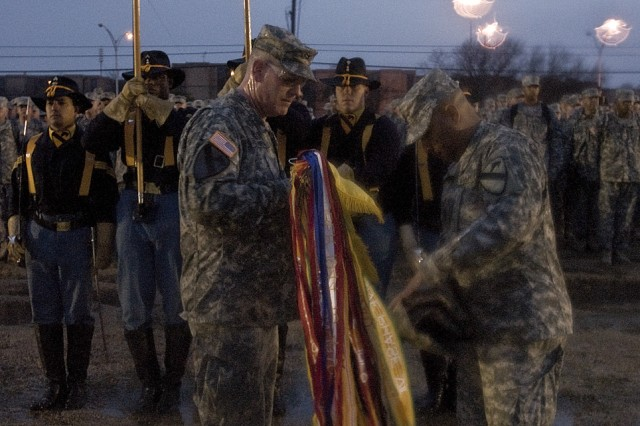 As freezing rain fell hard on Fort Hood's Cooper Field, 1st Brigade Combat Team commander, Col. Tobin Green (left), and the Brigade Command Sergeant Major, James Norman, uncase the brigades colors signifying the return of the 'Ironhorse brigade.' About 270 Soldiers returned to from a year-long deployment in support of Operation Iraqi Freedom 09-10.