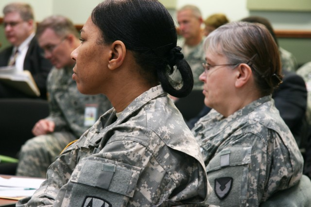 Col. Darlette Stowers, Logistics Civilian Augmentation Program Support Unit, and Col. Vicki Baxter, ASC Army Reserve Element, watch a briefing during the ASC Commanders Conference that took place Jan. 19-22 at ASC Headquarters on Rock Island Arsenal, Ill.
