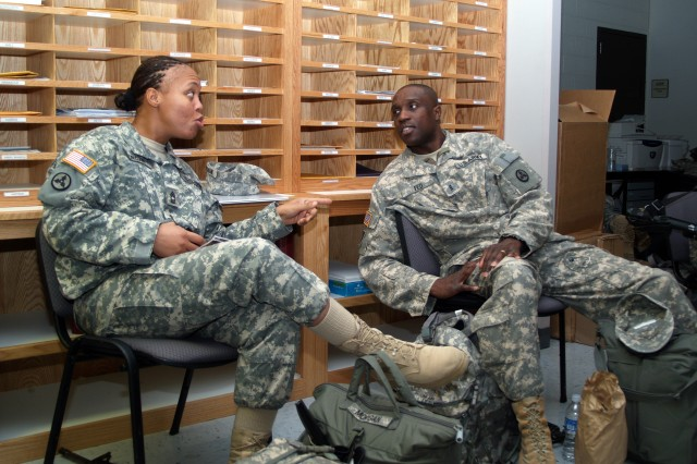 Master Sgt. Jacquelyn Morgan and Chief Warrant Officer Mark Fed, share conversation while waiting to board an Air Force C-17 aircraft bound for Haiti.  The 3d ESC Soldiers deployed to Haiti Wednesday, Jan. 27, to form Joint Logistics Task Force - Haiti, led by 3d ESC commander, Col. (Promotable) Robin Akin, and provide logistical expertise to the relief effort. (U.S. Army Photo by Spc. Michael Behlin)