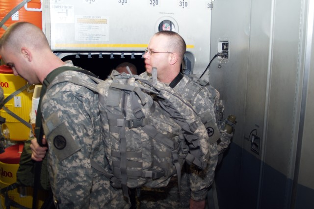 Private 1st Class Aaron Weimer and Staff Sgt. Cecil Billings of Fort Knox's 3d Sustainment Command (Expeditionary) wait to be seated aboard an Air Force C-17 aircraft. The Soldiers boarded the aircraft as the unit deployed to Haiti to form Joint Logistics Task Force - Haiti, which is led by Col. (P) Robin Akin, 3d ESC commander. (U.S. Army photo by Spc. Michael Behlin)