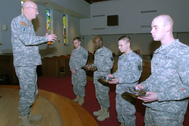 Chaplain (Lt. Col.) Kelly Moore, 10th Mountain Division chaplain, leads the chapel in prayer as the chaplain's assistants get ready to pass collection plates during a Haiti remembrance and relief service Jan. 22.