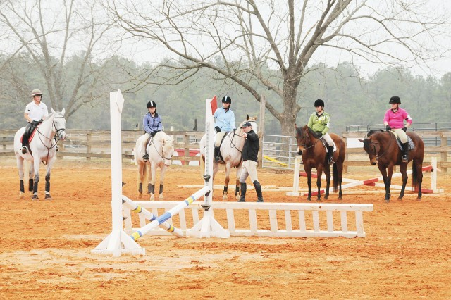 FORT RUCKER, Ala. - Area Pony Club members listen to Phillip Dutton's instructions during a clinic at the Riding Stables. He schooled them on proper flatwork and jumping techniques.