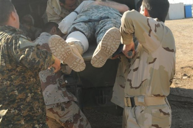 Iraqi Army medics with the Taji Location Command Medical Clinic Level 2 load a simulated victim into an emergency vehicle during a mass casualty exercise Jan. 27 at Camp Taji, Iraq.