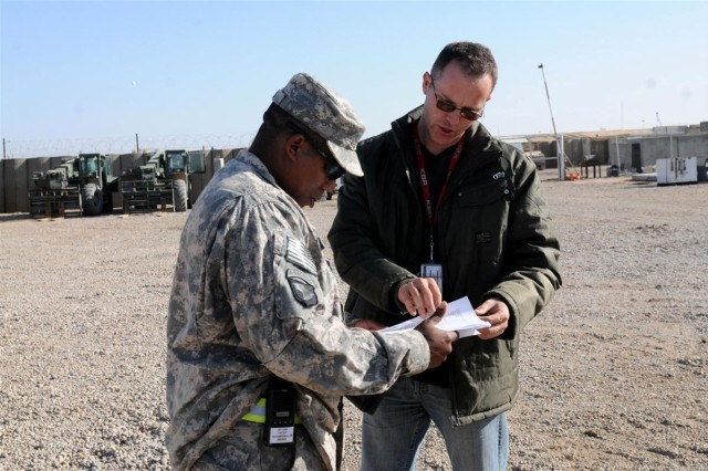 Sgt. Quintin E. L. Jones, the operations noncommissioned officer with the 159th Seaport Operations Company out of Fort Story, Va., and a Charlotte, N.C., native, assists a KBR, Inc. employee with filling out a transfer movement request Jan. 28, at the Central Receiving and Shipping Point at Contingency Operating Location Basra, Iraq.