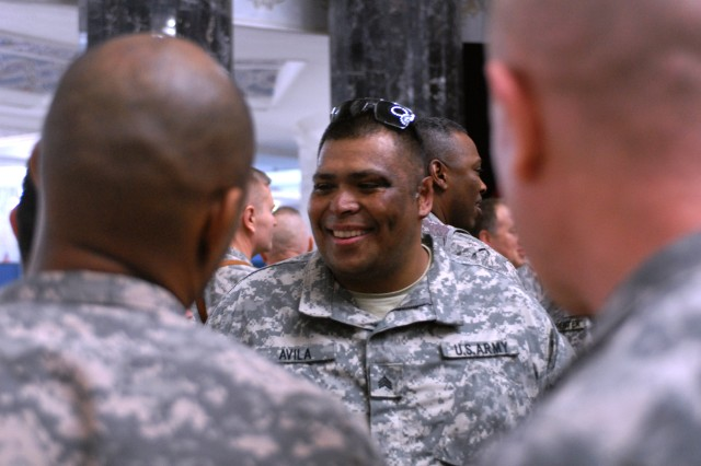 Sgt. Omar Avila (center) is greeted by servicemembers of all ranks after arriving in Baghdad Jan. 31. Avila, who was wounded by an improvised explosive device in 2007, has returned to Iraq with Operation Proper Exit in hopes in find emotional closure after his injury.