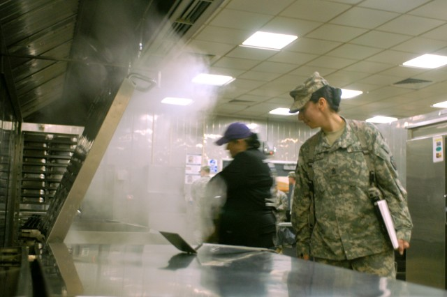 Sgt. Maj. Chantel Sena-Diaz, United States Forces-Iraq chaplain's office sergeant major, walks through a cloud of steam as she judges four teams participating in the Iron Chef competition Jan. 30, at Camp Victory's Sports Oasis Dining Facility in Baghdad, Iraq.
