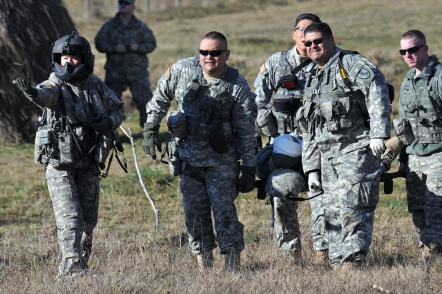 Sgt. 1st Class Marissa Burns, Columbia, S.C., an air ambulance crewmember, gives direction to Soldiers of Charlie Co., 1-144th Maneuver Task Force, as they carry a Soldier to a UH-60 Blackhawk helicopter for medical evacuation during a Quick Reaction Force exercise.