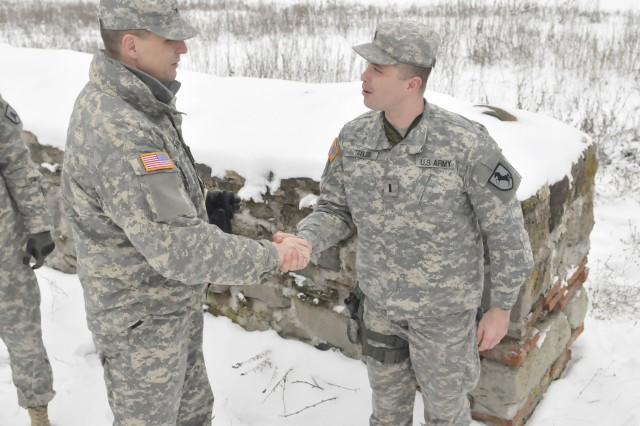 Brig. Gen. Al Dohrmann, Bismarck, N.D., commander of Multi National Battle Group – East, presents a special commander's coin to 1st Lt. Michael Taylor, Berkeley, Calif., a member of the 1-144th Maneuver Task Force, for his efforts in providing force protection at Camp Nothing Hill, Kosovo, a distant NATO outpost near the Administrative Boundary Line with Serbia. The award presentation took place Jan. 28 at the site of ancient Roman ruins near Camp Nothing Hill.