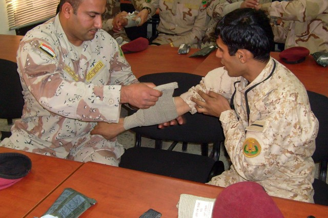 BAGHDAD - Taking time to practice what they have learned, Soldiers from the 11th Iraqi Army Field Engineer Regiment practice buddy aid as part of a basic medical training class, January 25, at the Old Ministry of Defense Building. Members of the 16th Engineer Brigade's medical team conducted the training class to help teach the 11th IA Soldiers basic first aid. (U.S. Army photo by Col. Mark Travovich, HHC 16th Engineer Brigade, USD-C)