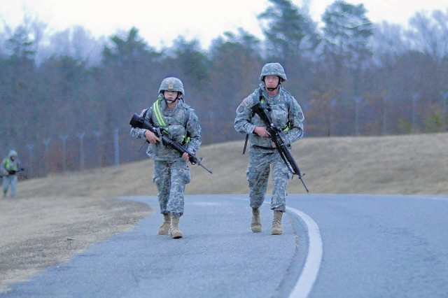 Spc. Allen Fary and Sgt. Jestin Llewellyn, members of the 55th Sustainment Brigade's Special Troops Battalion, take part in an early morning 5-kilometer march on Davison Army Airfield.