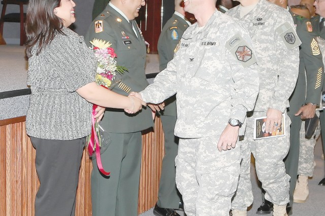 Colonel Timothy Faulkner, U.S. Army Garrison commander, Fort Huachuca congratulates Anna Garces, wife of retiring Sgt. 1st Class Steven Garces during Friday's Installation Retirement Ceremony in Fitch Auditorium. Sgt. 1st Class Steven Garces has 20 years of service. Sgt. Major Thomas Sanchez has 26 years of service. Both men and their families plan to reside in Sierra Vista. Chief Warrant Officer Four Rodney Thomas has 21 years of service. He and his family plan to reside in Covington, Ga.