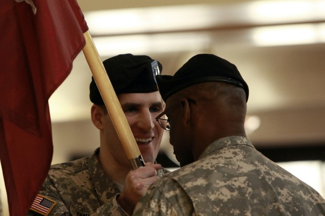 Captain Scott M. Smiley grins while passing the guidon back to 1st Sgt. Deon E. Dabrio during the  U.S. Army Warrior Transition Unit at West Point  change of command  ceremony Feb 1. The 2007 Army Times Soldier of the year is the first blind officer and second Wounded Warrior to hold a position of command.