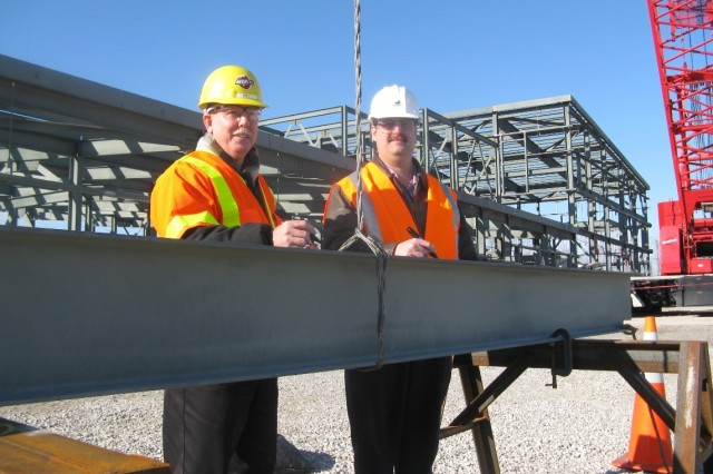 Signing the final beam for the Control and Support Building before it is lifted into place are project manager for Bechtel Parsons Blue Grass (left) and site project manager for the Assembled Chemical Weapons Alternatives (rights).