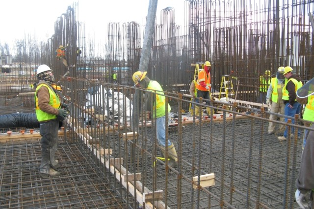 Construction workers make first concrete placement in the explosives containment area of the Munitions Demilitarization Building.